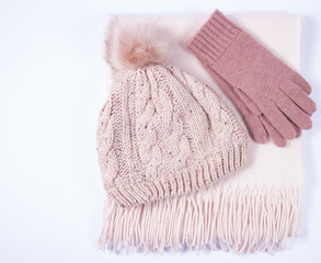 Warm winter knitted clothes - hat, scarf, gloves on a white background.