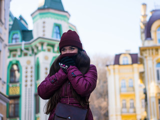 Pretty Brunette Girl Wearing Purple Winter Coat, Hat and Scarf, Walking by European Street at Winter, Wrapped up in a Scarf.