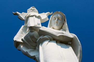 Giant statue of the Virgin Mary with Jesus in his arms against a blue sky close-up in Vung Tau.