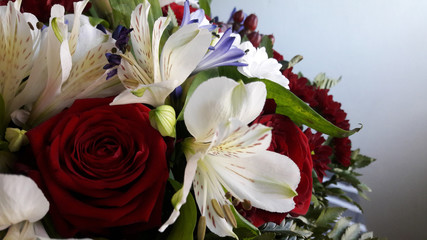 Bouquet of red roses and white and purple flowers for the lover