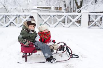 Little kids enjoy a sleigh ride. Child sledding. Children play outdoors in snow.