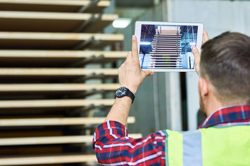 Back view portrait of factory worker taking picture of materials shipment via digital tablet, copy space
