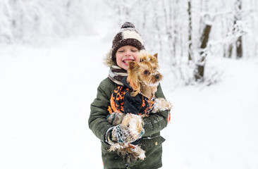Little boy and small doggy in winter park.