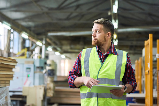 Waist up portrait of young man wearing reflective jacket holding digital tablet standing in factory warehouse, copy space