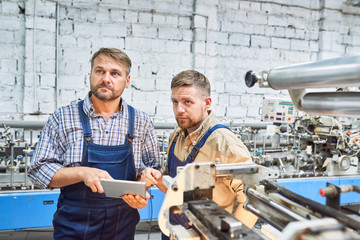 Portrait of two factory workers using modern machine at furniture factory operating it via digital tablet, copy space