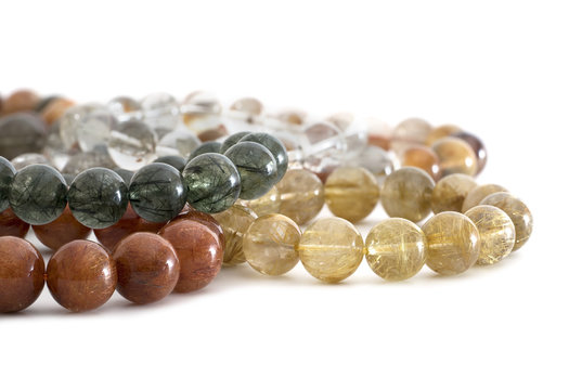 Beautiful translucent assorted colors Rutilated Quartz or Venus' hairstone bead in bracelets on white background