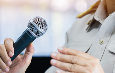 Thai Teacher Speaking in classroom or Conference meeting hall with Microphone of speech in seminar room on hall light bokeh background. Speaker Business tedtalk is vocalized form communication humans.