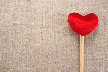 Red heart on a burlap background