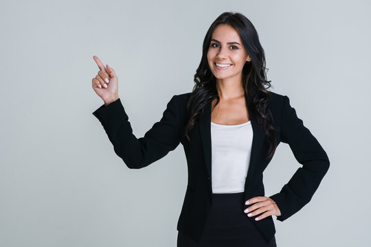 Take a look here! Beautiful young businesswoman pointing away and looking at camera with smile while standing against white background