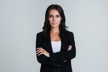 Confidant and beautiful. Beautiful young businesswoman looking at camera while standing against white background