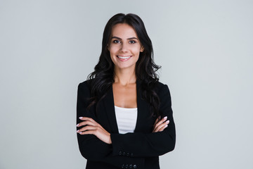 Perfect business lady. Beautiful young businesswoman looking at camera with smile while standing against white background Wall mural