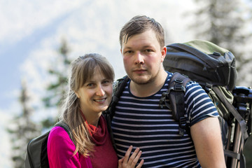 Portrait of couple of happy hikers in the countryside looking at camera.