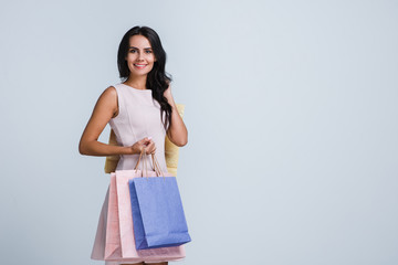 Successful shopping. Beautiful young woman holding shopping bags and looking at camera with smile while standing against white background