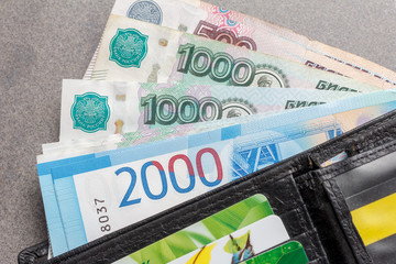 new Russian banknotes in denominations of 1000, 2000 and 5000 rubles and credit cards in a black leather purse close-up, top view