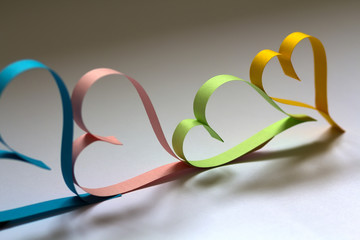 Valentine's day abstract background with cut paper colorful hearts on white.