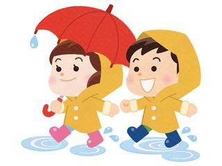 水たまりを歩く雨具を着た男の子と女の子