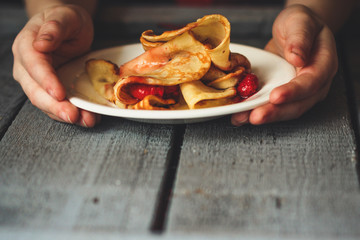 Pancakes (crepes) with berries and sweet jam