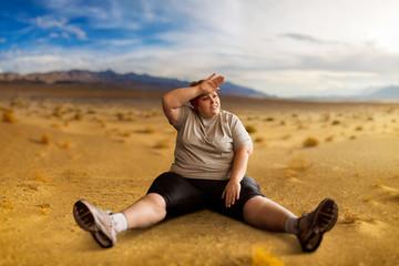 Overweight woman sitting in desert valley
