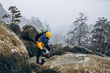 Happy tourist stands on the top of a rock over the mountains covered with snow