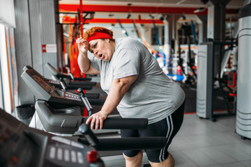 Overweight woman running on a treadmill in gym