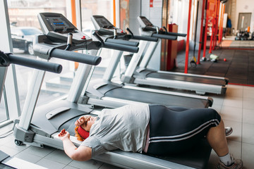 Overweight tired woman lies on a treadmill in gym