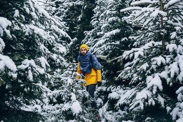 Bearded young man in a warm yellow hiking suit stands somewhere in the mountains covered with snow