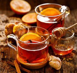 Hot tea, Spicy citrus hot tea with ginger, cloves, cinnamon and orange slices, delicious, warming and healthy in glass cups on a wooden table
