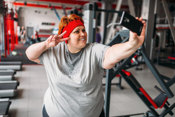 Fat woman makes selfie against exercise machines