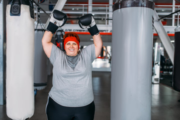 Overweight woman against punching bag in gym