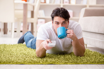 Man watching tv at home on floor