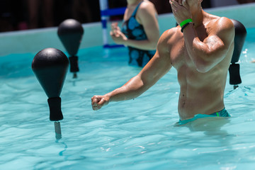 People Doing Water Aerobics with Boxing Speed Ball in an Outdoor Swimming Pool