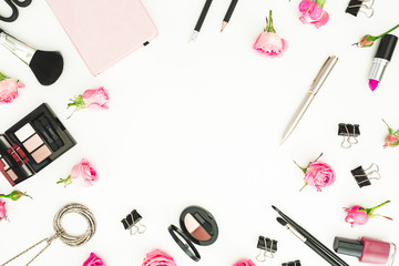 Workspace with cosmetics, accessories and pink roses on white background. Top view. Flat lay