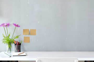 White wood desk with colour pencils, sticky note and flower with copy space.  workspace and designer accessories