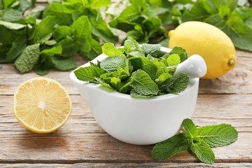 Fresh mint leafs in mortar with lemons on grey wooden table