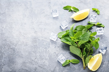 Mint leafs with lemons and ice cubes on grey wooden table