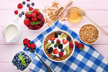 Tasty granola with berries in bowl, jug of milk and honey on pink wooden table