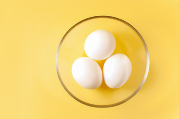 Three white eggs are lying in a round transparent glass cup in the middle of a yellow background.