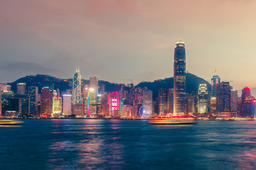 Scenic skyline of Hong Kong island, China, with skyscrapers and city illuminations at dusk. Multicolored travel background.