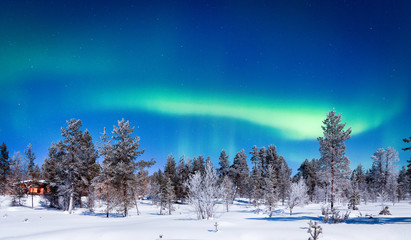 Aurora Borealis over winter wonderland scenery in Scandinavia