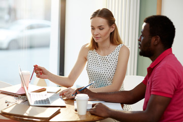 Young manager pointing at laptop display while making presentation to her colleague or discussing online data with him