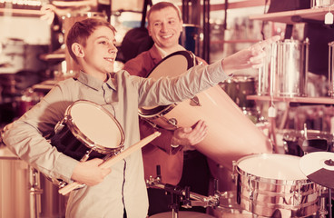 teenager and father deciding on ethnic drum in musical shop