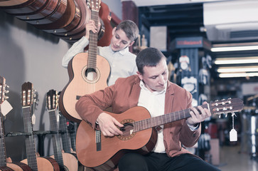 Boy and father are searching  acoustic guitar