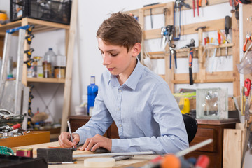 teenager  smiling and working with wood in the workshop