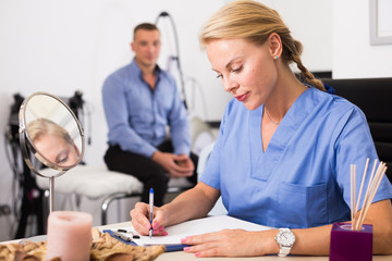 Woman specialist is writing the conclusion after procedure for man