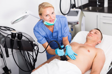 Female specialist is massaging with vacuum to belly of client for anti-fat
