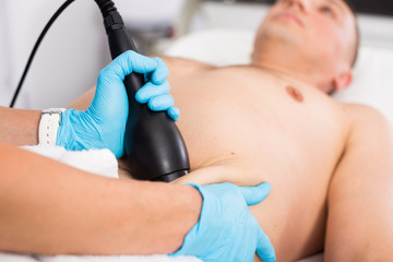 Woman doctor is doing vacuum massage procedure on belly of adult client