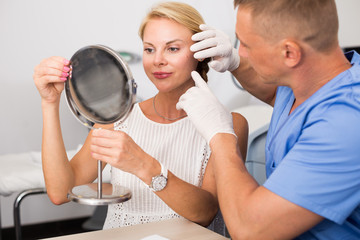 Man doctor is preparing female patient to procedure