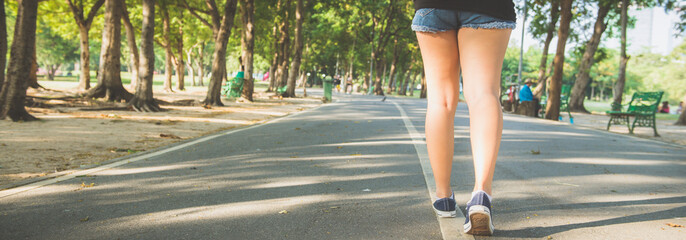 Asian woman's legs while jogging in the park covered with plenty of trees and warm sunlight. Young woman legs close up when running in the park. Outdoor activity in the park concept. Panoramic banner.