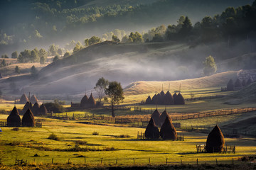 Beautiful rural mountain landscape in the morning light with fog, old houses and haystacks, Fundatura Ponorului, Hunedoara County, Romania