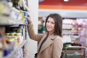 young woman buy can of tuna at supermarket